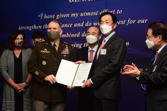 在韓米軍のエイブラムス司令官が13日に開かれた歓送行事で在韓米軍戦友会コリアチャプターのイ・ソヨン会長(予備役陸軍少将)から在韓米軍戦友会会員証を贈られた。[写真 在韓米軍戦友会]