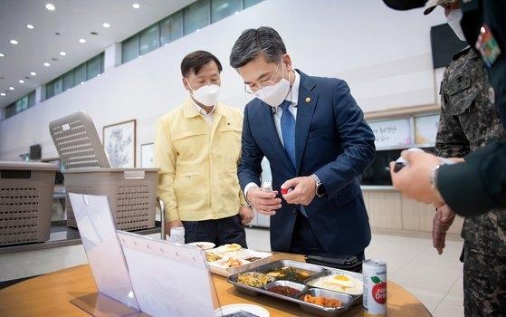 14日、韓国国防部の徐旭(ソ・ウク)長官が国防部領内の勤務支援団を訪れ、同団のキム・スンホ団長から隔離将兵用の給食や包装容器などについて報告を受けている。[写真 国防部]