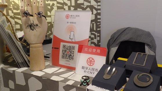 2月に北京の繁華街である王府井のショッピングモールのある店舗のレジにデジタル人民元決済端末が置かれている。QRコードとデジタル人民元電子ウォレットが設置されたスマートフォンを近づける決済方式の認識機能が書かれている。[中央フォト]