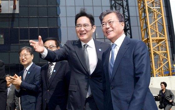 文在寅(ムン・ジェイン)大統領(右)が2019年4月30日午後、京畿道サムスン電子華城(ファソン)事業場で行われた「システム半導体ビジョン宣言式」を終えた後、李在鎔(イ・ジェヨン)サムスン電子副会長(右から2人目)の案内を受けながらEUV(極端紫外線)棟の建設現場を見回った。[青瓦台写真記者団]