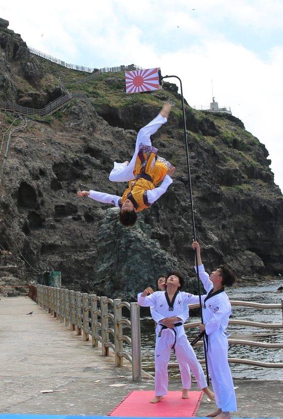 慶尚北道(キョンサンブクド)地域の体育関係者が旭日旗が描かれた板を粉砕している。[写真 慶北道体育会]