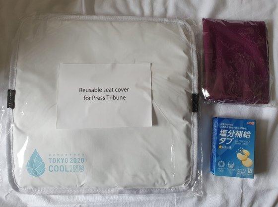 東京オリンピック(五輪)組織委がメディア関係者に配布した物品。左側がクールシート、右側は塩分補給タブ(下)とクールタオル。[写真 東京=ペ・チュンヒョン記者]
