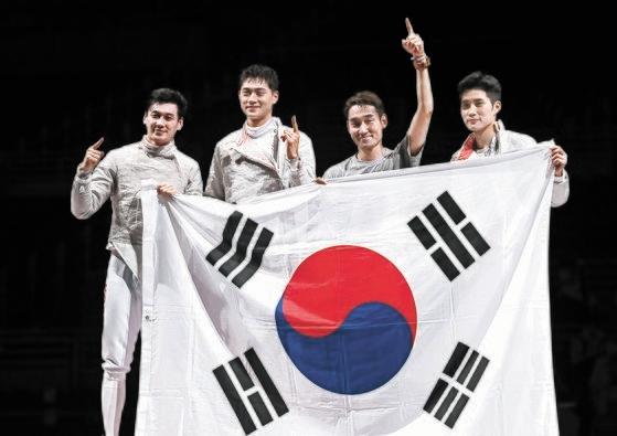 優勝を確定した直後、太極旗を広げて喜ぶク・ボンギル、オ・サンウク、キム・ジョンファン、キム・ジュンホ(左から)[写真 オリンピック写真共同取材団]