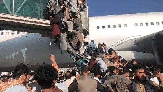 アフガニスタン首都カブールのハミド・カルザイ空港で16日、同国から脱出しようとする人々が扉が開かれた飛行機に搭乗しようと必死にボーディング・ブリッジに這い上がっている。[写真 ツイッター キャプチャー]