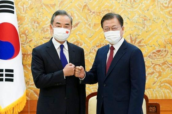 韓国の文在寅(ムン・ジェイン)大統領が15日、青瓦台(チョンワデ、大統領府)で王毅中国外交部長と面会した。文大統領が面会に先立ち記念撮影をした後、王部長とグータッチをしている。[写真 青瓦台写真記者団]