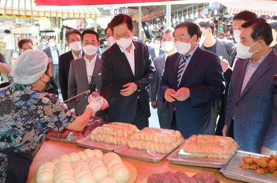 韓国与党「共に民主党」の宋永吉(ソン・ヨンギル)代表が秋夕(チュソク、中秋)を控えた16日午前、ソウル中区の南大門(ナムデムン)市場を訪問してマンドゥ(韓国式餃子)を購入している。〔写真 国会写真記者団〕