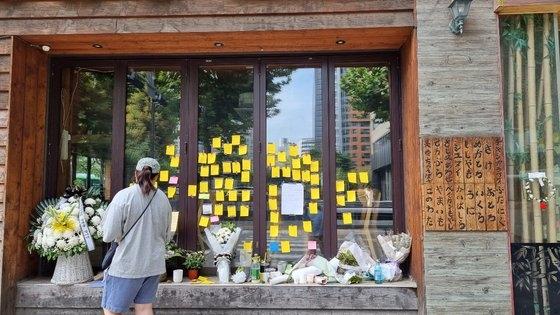 今月27日、ソウル麻浦(マポ)にある居酒屋の女性社長が運営していた店舗のガラス壁に市民が残した追慕メモが貼り付けられている。その下に置かれた小さな花輪のリボンには「自営業者のご冥福をお祈りします」と書かれている。チョ・ガンス記者