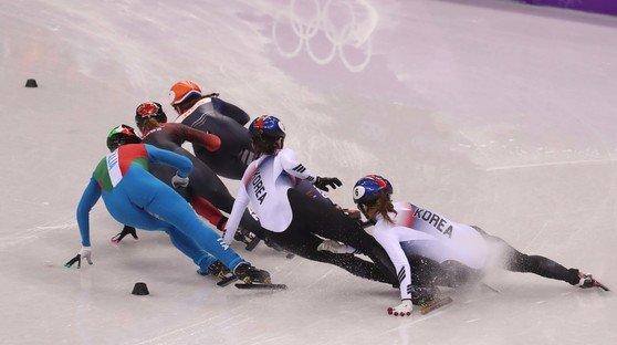 2018年韓国で開催された平昌(ピョンチャン)オリンピック(五輪)ショートトラック女子1000メートル決勝で沈錫希(シム・ソクヒ、右から2人目)は追い越しをかけてきた崔ミン禎(チェ・ミンジョン、右)ともつれて転倒した。[中央フォト]