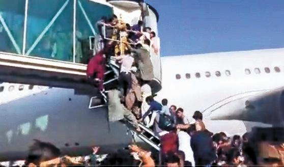 イスラム武装組織タリバンが政権を再掌握した今年8月16日、首都カブール空港からアフガニスタンを脱出しようとする人々が航空機に乗ろうと搭乗ブリッジにぶらさがり混乱を来している。[写真 ツイッター キャプチャー]