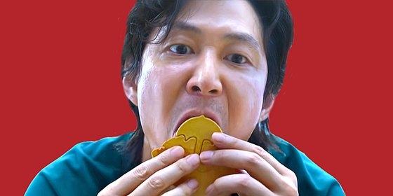 Netflix(ネットフリックス)のオリジナルシリーズ『イカゲーム』で主人公イ・ジョンジェがタルゴナをなめて溶かす場面。[写真 Netflix]